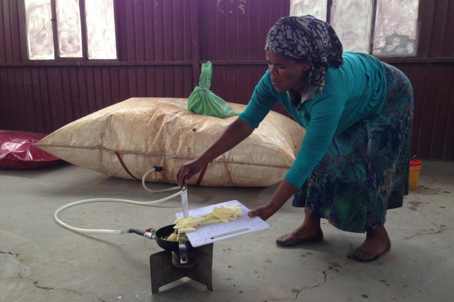Eine Afrikanerin frittiert Pommes in einer Pfanne auf einen Gaskocher, der mit Biogas angeheizt wird. Im Hintergrund liegt ein Biogas-Rücksack, der an den Gaskocher angeschlossen ist.
