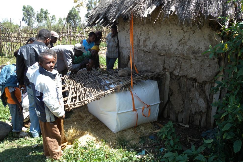 Einheimischen in einem Entwicklungsland wird gezeigt, wie ein mit Biogas gefülltes Staupolster zur Energiegewinnung an den Stromkreis angeschlossen wird.