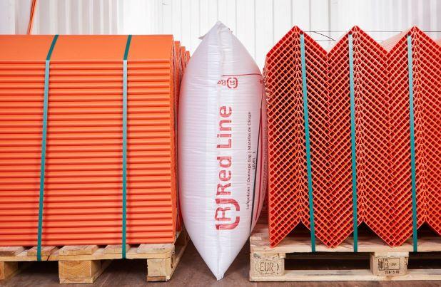 Ein Red Line Staupolster in Übergröße zwischen zwei Paletten mit orangenen Kantenschutzwinkel beladen.
