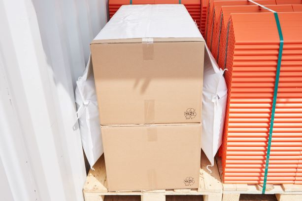 A saddle bag with two dunnage bags on each side secures cartons on a pallet in a container. Next to them orange edge protectors.