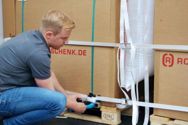 Ein Mitarbeiter der GmbH Rothschenk spannt ein White Lash Gurtband mit einen Haspelspanner an zwei Paletten in einem Container.