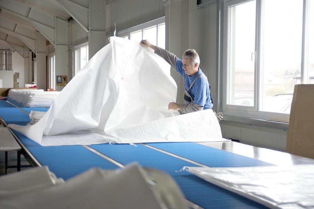 Ein Mitarbeiter der G&H GmbH Rothschenk klappt einen fertiggenähten Stausack auf.