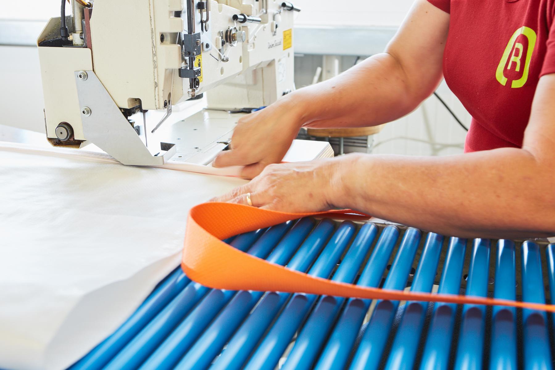Eine Mitarbeiterin der G&H GmbH Rothschenk näht ein Gurtband an einen Staupolster.