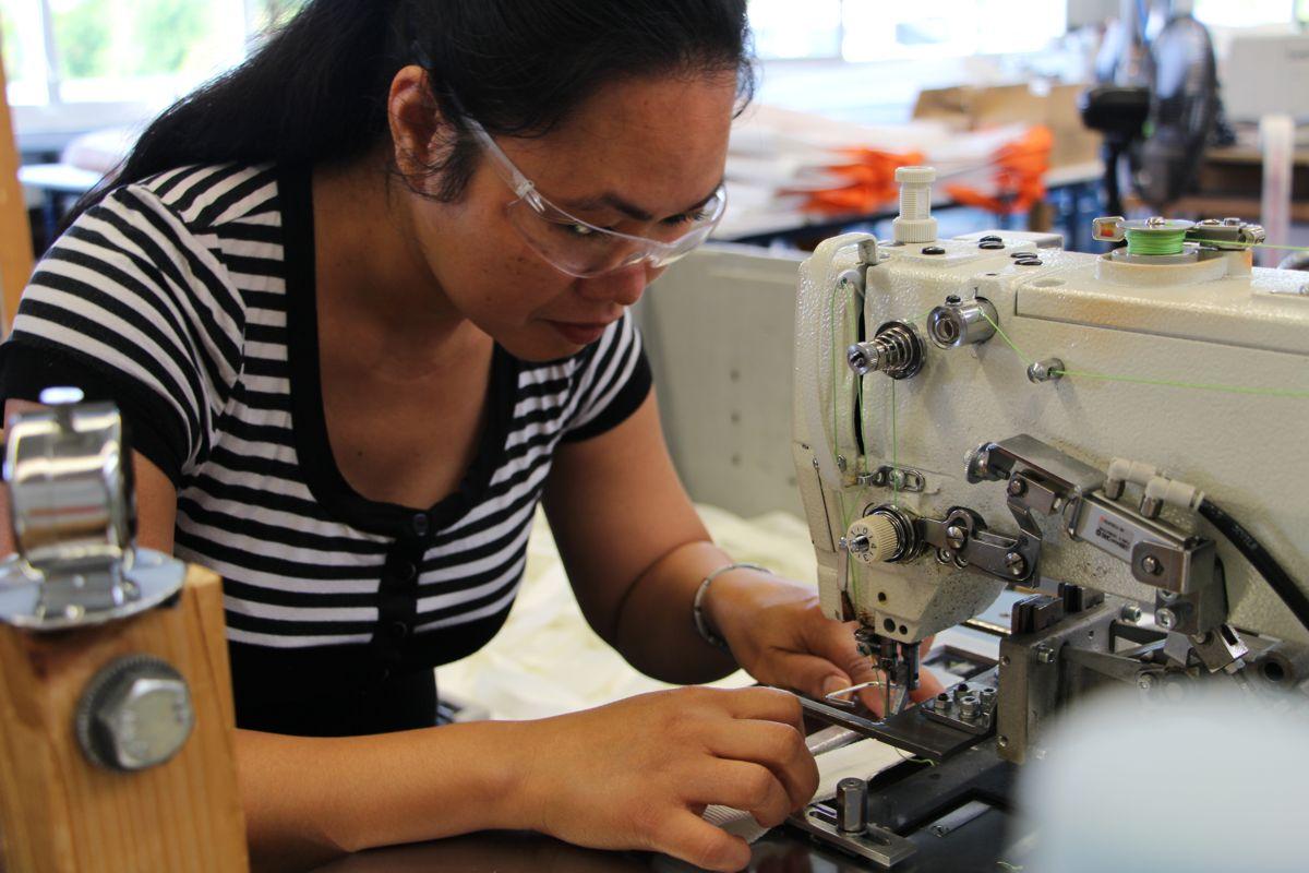 Eine Mitarbeiterin mit Sicherheitsbrille näht eine Schlaufe in ein Lashing ein.