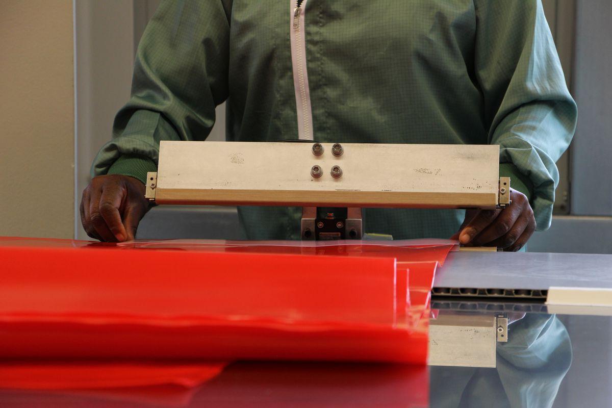 Eine Mitarbeiterin der G&H GmbH Rothschenk schweißt ein Ventil an einen roten Stausack fest.