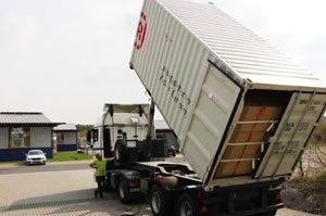 Ein geladener Container vollziehr einen Kipptest für die Ladungssischerung.