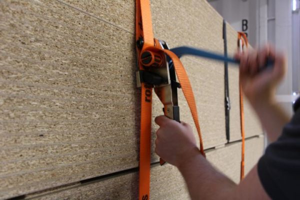 Spanplatten werden mit einem Haspelspanner und Gurtbändern gesichert.