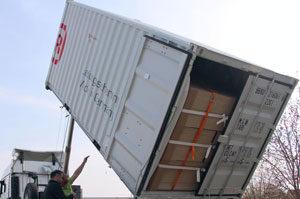 Ein Container mit offener Tür wird gekippt, um zu testen, ob die gesicherte Ware nicht verrutscht.