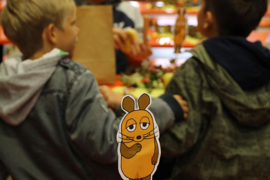 """Zwei Jungen stehen vor einem Tisch. Im Vordergrund ist eine Papierfigur der orangenen Maus aus der """"Sendung mit der Maus"""""""