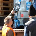 Zwei Kollegen sichern einen IBC mit einem Zurrgurt auf einem LKW