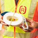 Ein Mitarbeiter mit gelber Sicherheitsweste der G&H GmbH Rothschenk hält eine zusammengerolltes Gurtband mit Sicherungshaken.