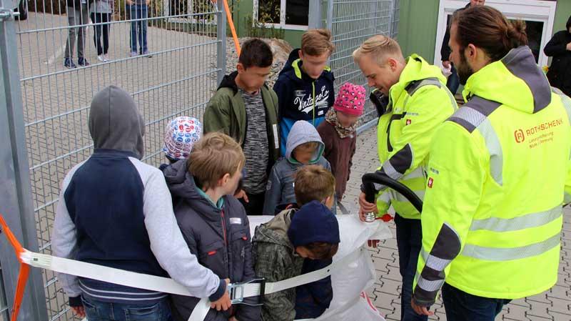 Unsere Mitarbeiter André Bauer und Francisco Jimenez demonstrieren einer Gruppe Kindern die Anwendung von Staupolstern und Gurtbändern zur Ladungssicherung.
