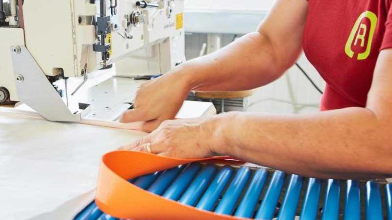 Eine Näherin der G&H Rothschenk GmbH verknüpft einen Stausack mit einen Gurtband zu einen individuellen Set.