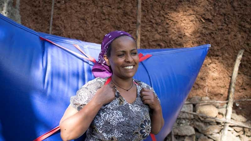 Eine Afrikanerin trägt ein mit Biogas gefülltes Staupolster auf den Rücken.
