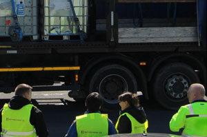 Vier gelbe Westen tragende Mitarbeiter stehen bei einer Schulung vor einem LKW, der zur Seite geöffnet ist und einen Bremstest absolviert.