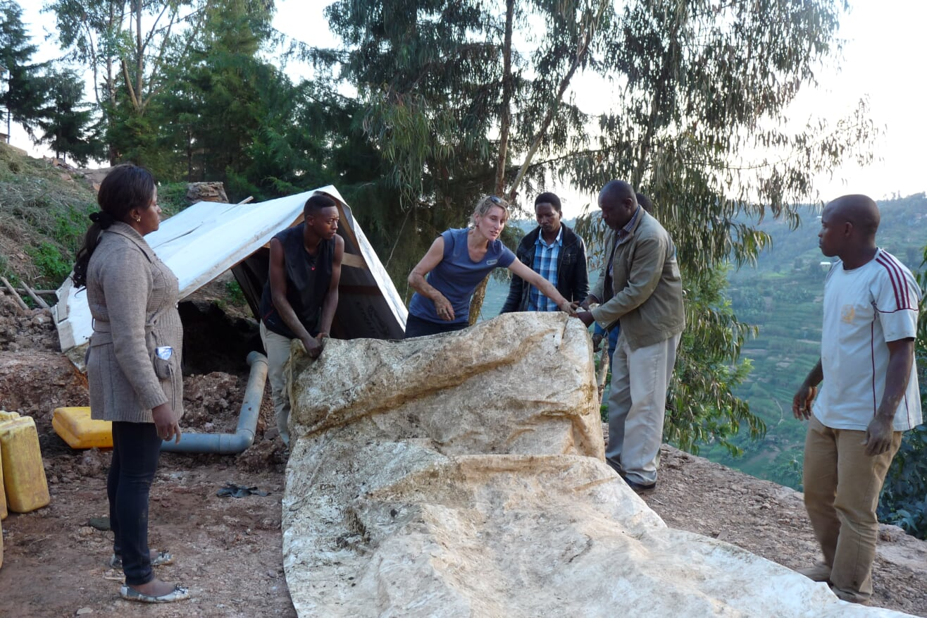 Eine Entwicklungshelferin zeigt sechs Einheimischen, wie man einen Stausack in Übergröße mit Biogas befüllt.
