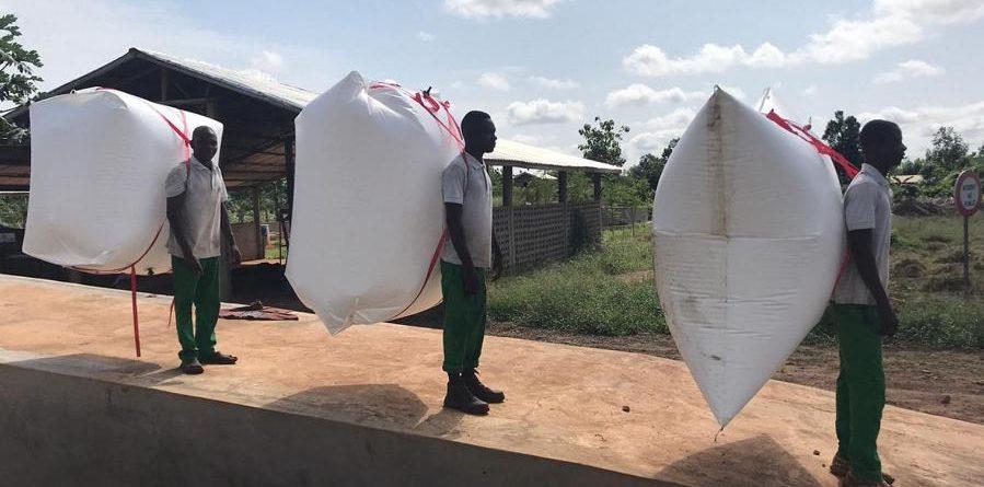 Drei Afrikaner mit Biogas-Rücksäcken auf den Rücken stehen auf einer Rampe.