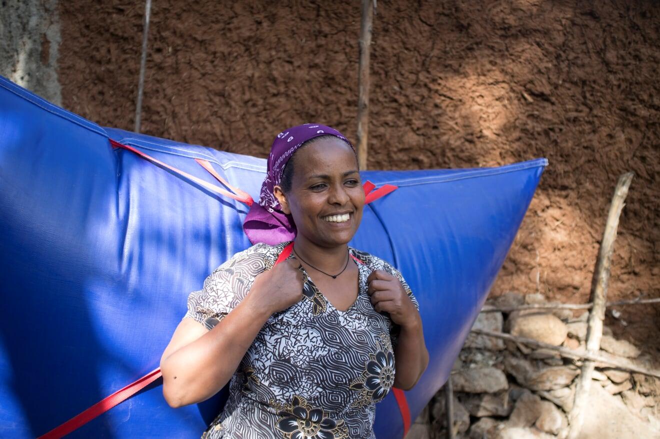Eine Einheimische trägt ein blaues Staupolster auf den Rücken, das mit Biogas befüllt ist.