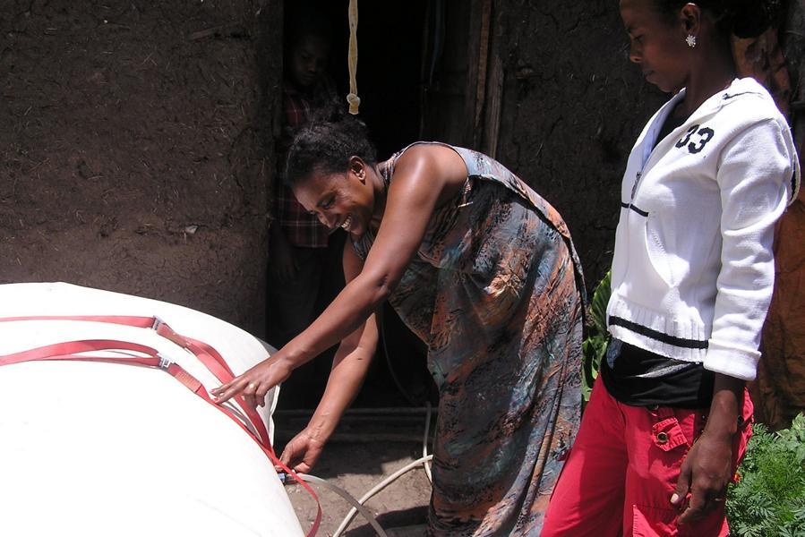 Eine lächelnde Afrikanerin zeigt einer weiteren Einheimischen, wie man einen Biogas-Rücksack an einen Stromkreis anschließt.