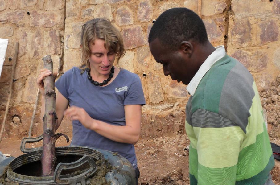 Eine Entwicklungshelferin rührt mit einem Ast in einem Biogas-Silo. Dabei berät sie einen Einheimischen.
